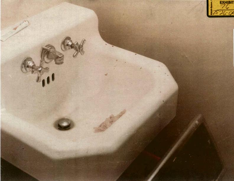 Sink in hall bathroom, with portion of stepladder (bottom right) and pink tissue (CID Exhibit D49) in sink