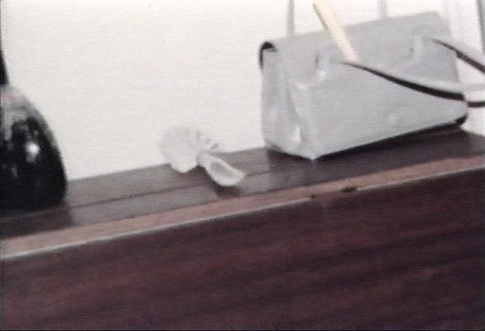 Clear-handled hairbrush next to purse on sideboard in dining room near kitchen